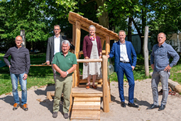 Sechs Personen am neuen Spielhaus im Garten des Schulkindergartens.