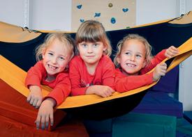 Drei kleine Mädchen liegen nebeneinander in einer Hängematte und lachen in die Kamera.