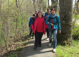 Eine Frau mit Behinderung geht am Arm einer Assistenzkraft im Wald spazieren. Weitere Menschen laufen hinter ihnen.