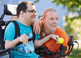 Ein Mann im Rollstuhl und sein Assistent blicken zusammen in die Ferne.
