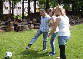 Ein Mann kickt einen Fußball auf einer Wiese und wird dabei von zwei Betreuerinnen gestützt.