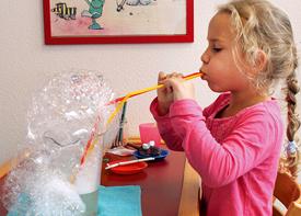 Ein Mädchen bläst mit einem langen Strohhalm in eine Gefäß und macht Schaumblasen.