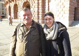 Ein Mann und eine Frau stehen vor einem historischen Gebäude und lachen in die Kamera.