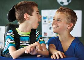 Ein Junge im Rollstuhl lacht einen anderen Jungen an.