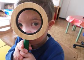 Ein kleiner Junge hält sich eine große Lupe vors Gesicht und blickt den Betrachter an.