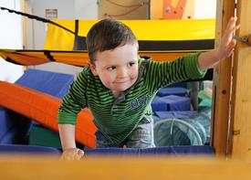 Ein kleiner Junge klettert über eine Matte zu einer Sprossenwand.