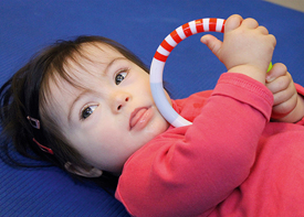 Ein kleines Mädchen liegt auf einer Matte und hält einen Greifring in den Händen.