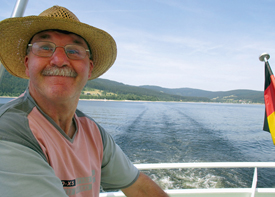 Ein Mann sitzt auf einem Schiff, das über das Meer fährt.