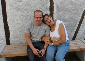 Ein Mann und eine Frau sitzen lachend auf einer Bank vor einem Haus.