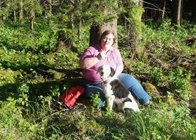 Eine Frau mit Behinderung sitzt an einen Baum gelehnt im Wald und genießt den Sonnenschein.