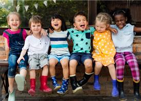 Sechs Kinder sitzen in einer Reihe auf einer Bank