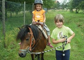 Ein Mädchen reitet auf einem Pony, das von einem anderen Mädchen an einer Pferdeleine geführt wird.