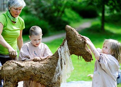 Zwei Kinder und eine Erzieherin gestalten im Freien ein Pferd aus Lehm.