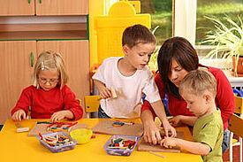 Eine Förderkraft sitzt mit drei Kindern am Tisch und unterstützt diese beim Basteln.