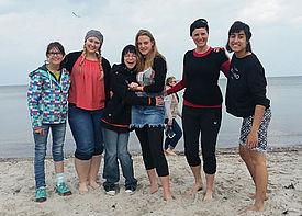 Eine Gruppe von sechs Menschen steht an einem Strand und lacht.