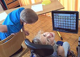 Ein Mädchen im Rollstuhl sitzt vor einem Talker. Sie dreht den Kopf nach oben und lächelt in die Kamera.