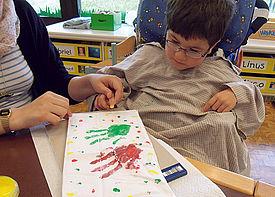 Ein kleiner Junge im Rollstuhl malt mit Hilfe einer Assistenzkraft ein Bild.