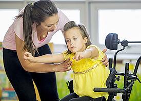 Eine Erzieherin hebt ein Mädchen aus einem Rollstuhl.
