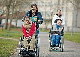 Eine Assistenzkraft schiebt einen Jungen im Rollstuhl durch den Park. Im Hintergrund ist ein zweiter Junge zu sehen, der ebenfalls geschoben wird.