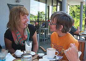 Zwei Frauen unterhalten sich in einem Café draußen auf einer Terrasse.
