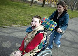 Ein Junge im Rollstuhl wird von einer Assistenzkraft durch einen Park geschoben.