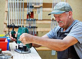 Ein Mann sitzt an der Werkbank und sägt mit einer Stichsäge in ein Brett.