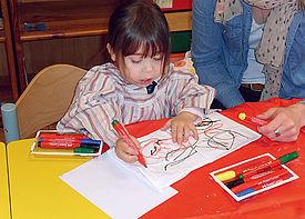 Ein kleines Mädchen malt mit Buntstiften. Neben ihr sitzt eine Schulbegleiterin.