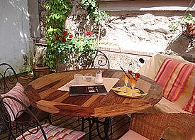 Auf einer Holzterrasse steht ein Tisch mit fünf Stühlen. Auf dem Tisch liegt eine Speisekarte und ein Tablett mit zwei Gläsern.