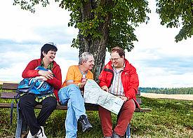 Drei Wanderer sitzen auf einer Bank unter einem Baum und schauen sich  eine Landkarte an.