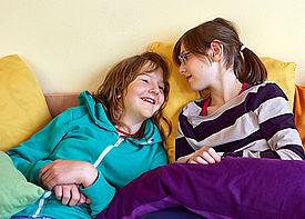 Zwei Mädchen liegen gemütlich auf einem Sofa und unterhalten sich.