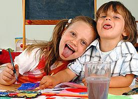 Ein Junge und ein Mädchen malen mit Wasserfarben und strecken der Kamera die Zunge raus.