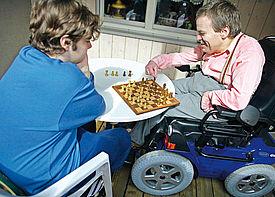Ein Mann im Rollstuhl spielt mit einer Assistenzkraft Schach.