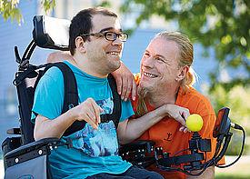 Ein Mann im Rollstuhl unterhält sich mit einem Betreuer draußen in einem Garten.