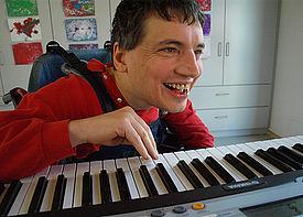 Ein Mann im Rollstuhl spielt auf einem Keyboard.