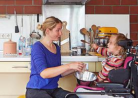 Ein Mädchen im Rollstuhl sitzt mit einer Assistenzkraft in einer Küche. Sie rühren zusammen in einer Schüssel.