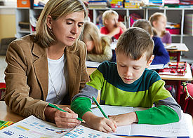 Ein Junge und eine Schulbegleiterin sitzen im Klassenzimmer. Der Junge löst mit Hilfe der Schulbegleiterin eine Aufgabe.