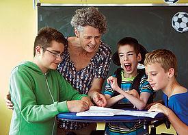 Drei Jungs mit Behinderung und eine Lehrerin sind im Klassenzimmer. Sie stehen an einem Tisch und beugen sich über ein Heft.