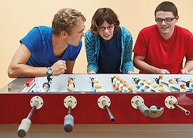 Zwei Teenager und ein Teilnehmer des Freiwilligendienstes stehen gemeinsam am Tischkicker.