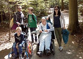 Zwei Kinder im Rollstuhl stehen im Wald zusammen mit zwei Betreuern und einem weiteren Jungen.