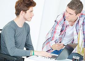 Ein junger Mann im Rollstuhl sitzt vor einem Laptop, auf dem ihm eine Assustenzkraft etwas zeigt.