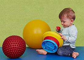 Ein kleiner Junge sitzt auf einer Behandlungsmatte und spielt mit einem Kreisel.