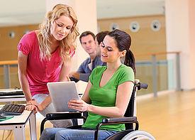 Eine Frau im Rollstuhl zeigt einer neben ihr stehenden Assistenzkraft ein Dokument.