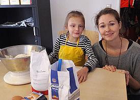 Ein Mädchen mit Behinderung sitzt vor einem Tisch mit Backutensilien. Neben ihr kniet eine Assistenzkraft.