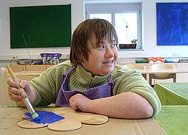 Eine Frau sitzt an einem Tisch und malt mit einem Pinsel ein Stück Holz in Form einer Blume an.
