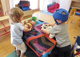 Zwei kleine Kinder mit Behinderung stehen an einem Tisch und wickeln eine Puppe.