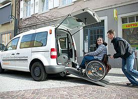 Eine Assistentkraft schiebt eine Frau in einem Rollstuhl eine Rampe hinauf in ein Auto.