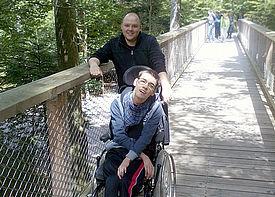 Ein Mann in einem Rollstuhl ist mit einer Assistenzkraft auf einem Baumwipfelpfad.