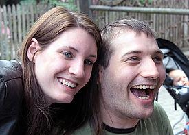 Ein Mann und eine Frau stehen dicht nebeneinander und lachen.