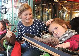 Ein Mädchen im Rollstuhl ist mit einer Assistenzkraft in einem Café.