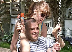 Ein Mann mit Behinderung sitzt auf einer Schaukel und wird von einer Assistenzkraft angeschoben.